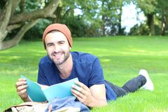 Cheerful student reading in the park with copy space.  Stock Image
