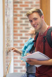 Cheerful student searching something on notice board Stock Photos