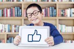 Cheerful student shows thumb up icon in library. Portrait of a little boy smiling at the camera while showing a thumb up symbol with a digital tablet in the Stock Images