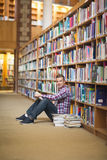 Cheerful student sitting on library floor reading Royalty Free Stock Images