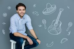 Cheerful student smiling and dreaming about a party in Mexican style. Mexican style. Positive creative young man sitting on the chair and looking curious while Royalty Free Stock Image