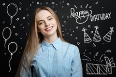 Cheerful student smiling while having her birthday party. Happy birthday. Emotional young beautiful girl feeling happy and smiling cheerfully while being at her Stock Photos