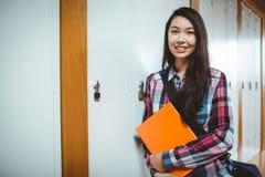 Cheerful student standing next the locker Stock Photo