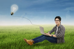 Cheerful student studying outdoors. Male student studying with laptop on the park Stock Image