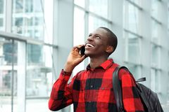 Cheerful student talking on cell phone at station. Portrait of cheerful young african student talking on cell phone at station Stock Photography