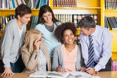Cheerful Student With Teachers And Classmates In. Portrait of cheerful female student with teachers and classmates in university library Royalty Free Stock Images