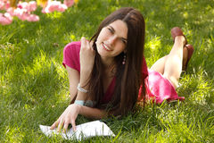 Cheerful student teen girl reading book on green spring grass Stock Images