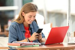 Cheerful student texting on phone in a bar stock photos