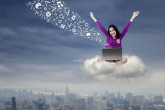 Cheerful student uses laptop on the cloud Royalty Free Stock Photography