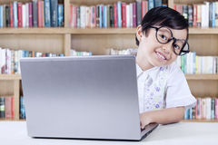 Cheerful Student Using Laptop in The Library. Cheerful female elementary school student using a laptop in the library Royalty Free Stock Image