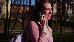 Cheerful student walking in park and talking by smartphone in slow motion. Happy student strolling in park and speaking by smartphone in slow motion. Concept of stock footage