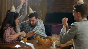 Cheerful students with confetti celebrating birthday party in a cafe. Slow motion. Professional shot in HD resolution. 088. You can use it e.g. in your stock video footage
