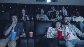 Cheerful students enjoying interesting movie in cinema sitting in dark room. Together looking at screen with happy faces. Modern culture and entertainment stock video