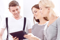 Cheerful students holding tablet computer Royalty Free Stock Images