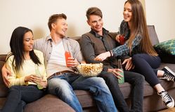 Cheerful students with laptop on a sofa Stock Photos