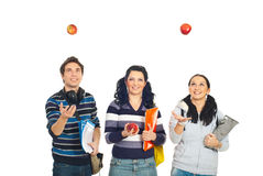 Cheerful students playing with apples Stock Images