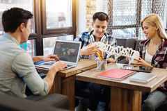 Cheerful students studying genetics. Like what you do. Cheerful smart students sitting at the table and doing project while studying genetics royalty free stock image