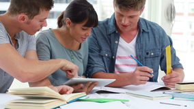 Cheerful students talking together while studying Royalty Free Stock Images