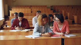 Cheerful students are using smartphones and chatting during break between lectures at university. Modern technology. Cheerful students multiethnic group are stock video footage