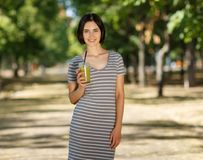 Smiling female with a green smoothie. Healthy women on a blurred park background. Healthy lifestyle concept. Copy space. Royalty Free Stock Images