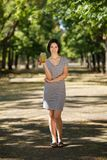 Smiling female with a green smoothie. Healthy women on a blurred park background. Healthy lifestyle concept. Copy space. Royalty Free Stock Photos