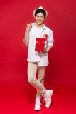 Cheerful stylish asian young male man holding a gift  on Stock Photo