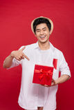 Cheerful stylish asian young male man holding a gift  on Royalty Free Stock Photos