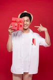 Cheerful stylish asian young male man holding a gift  on Royalty Free Stock Photo