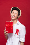 Cheerful stylish asian young male man holding a gift  on Stock Photos