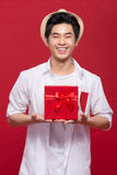 Cheerful stylish asian young male man holding a gift  on Royalty Free Stock Image