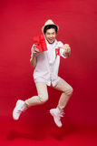 Cheerful stylish asian young male man jumping and holding a gift Royalty Free Stock Photo