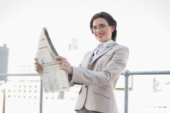 Cheerful stylish brown haired businesswoman reading a newspaper Royalty Free Stock Photo