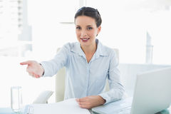 Cheerful stylish brunette businesswoman presenting her hand Stock Photography