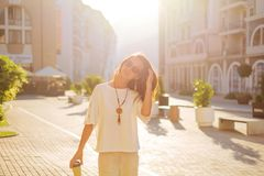 Cheerful woman walking in city in spring morning. Cheerful stylish brunette young woman walking with paper cup of coffee in city street in spring morning royalty free stock images
