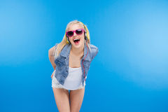 Cheerful stylish female teenager. Posing over blue background royalty free stock photos