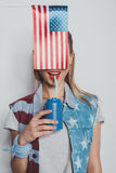Cheerful stylish girl in american patriotic outfit drinking soda from can, with american flag in front of her face Royalty Free Stock Photo