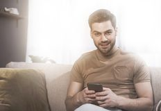 Cheerful stylish guy is relaxing at home with phone royalty free stock photo