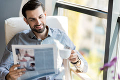 Cheerful stylish guy resting with cup of espresso and newspaper. Enjoying press. Portrait of joyful stylish young man is drinking coffee and reading news while Royalty Free Stock Photography