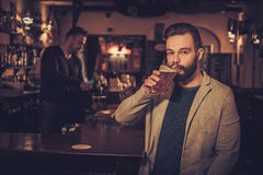 Cheerful stylish man with a pint of draft beer at bar counter in pub. Cheerful stylish men with a pint of draft beer at bar counter in pub stock image