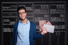 Cheerful stylish man presenting personal organisers. Stock Photography