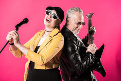 Cheerful stylish senior couple of rock and roll musicians performing Stock Image