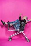 Cheerful stylish senior man having fun while sitting in shopping trolley Royalty Free Stock Photography