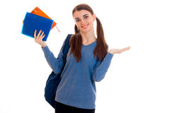 Cheerful stylish student girl with pigtails and backpack on her shoulders smiling on camera with books in her hands Stock Photography