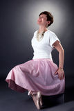 Cheerful stylish woman posing in pointes. On gray background Royalty Free Stock Photography