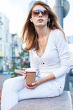 Cheerful stylish young woman drinking coffee outside on urban background Stock Photo
