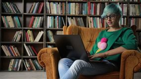 Happy freelance entrepreneur working with laptop. Cheerful successful freelancer girl in eyeglasses working on her laptop while sitting in comfortable chair at stock video footage