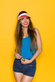 Cheerful Summer Girl. Smiling girl in blue shirt, red sun visor and jeans shorts poses against yellow wall and plays with her hair. Three quarter length studio Stock Photo