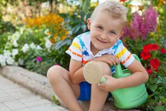 A cheerful, suntanned blond boy sits by the flower bed with brig Stock Photos