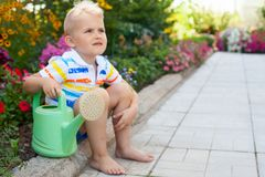 A cheerful, suntanned blond boy sits by the flower bed with brig Royalty Free Stock Photo