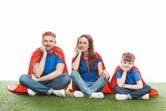 Cheerful super family sitting on lawn and smiling at camera. On white stock photos